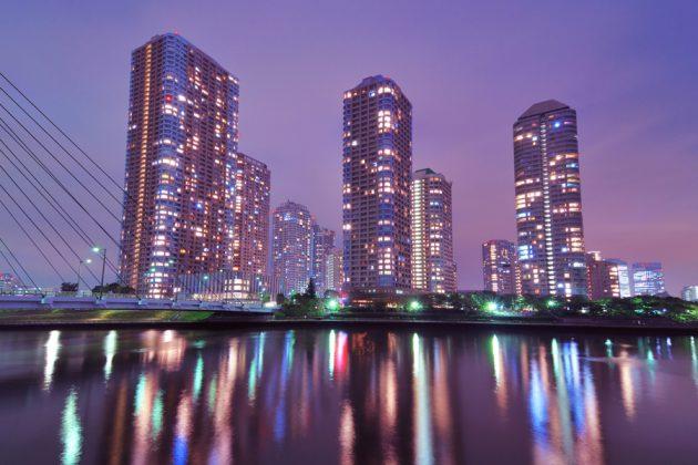 En kvällsupplyst Tokyo skyline med floden Sumida i förgrunden.