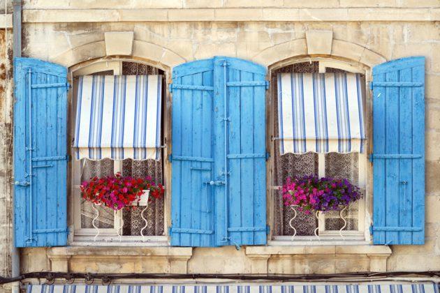 Vackra, gamla fönster med blå fönsterluckor i Arles, Frankrike.