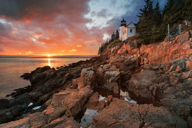 Solnedgång över fyr vid klippor.