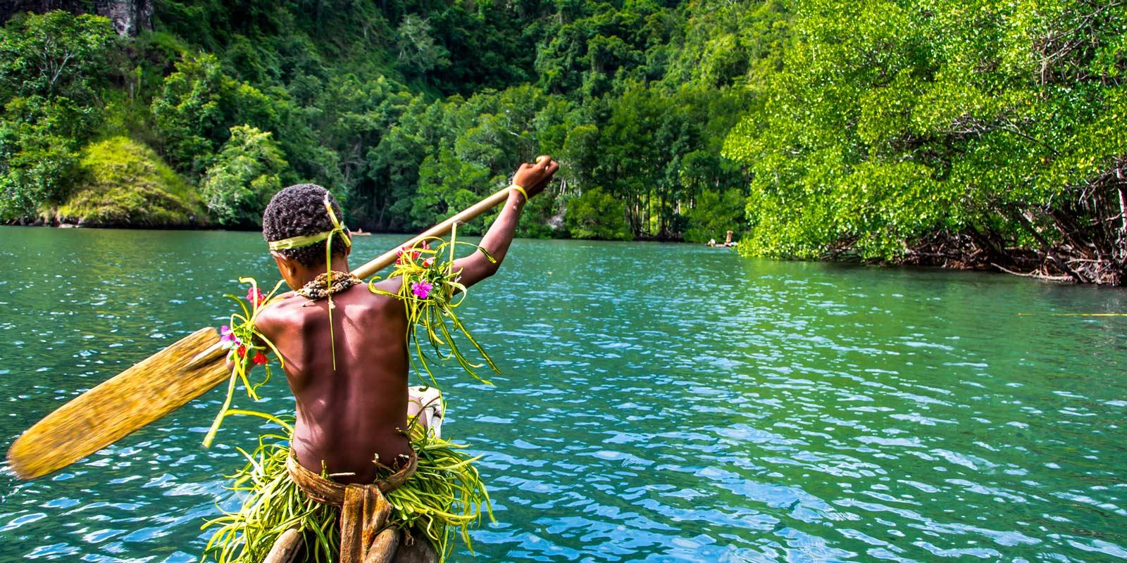 Pojke paddlar traditionell kanot i grönskande omgivningar Papua Nya Guinea.